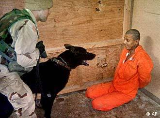 A US soldier holding a dog in front an Iraqi detainee at Abu Ghraib prison on the outskirts of Baghdad.