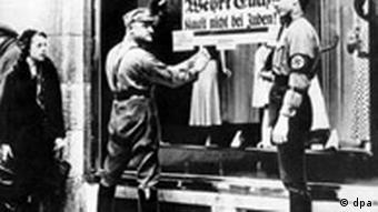 SA-Männer kleben während des Dritten Reiches ein volksverhetzendes Plakat mit der Aufschrift Deutsche! Wehrt Euch!