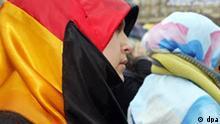 Eine junge Frau trägt am 24.1.2004 bei einer Demonstration in Köln ein Kopftuch in den Farben der deutschen Fahne. Unter dem Motto Es reicht! Wir wehren uns, dass Diskriminierung gesetzlich wird. Schluss mit der Pseudo- Religionsfreiheit protestierten zahlreiche Frauen und Mädchen vor dem Dom gegen ein Kopftuchverbot. Aufgerufen zu dem Protest hatte der Lokalkreis Köln der Organisation Muslimische Jugend in Deutschland. Auch Bundespräsident Rau hatte am 22.1. ein Kopftuchverbot verurteilt und für einen toleranten Umgang mit anderen Religionen geworben. Die in der Verfassung garantierte Religionsfreiheit gelte auch für den Islam. Rau zufolge könne man nicht ein religiöses Symbol verbieten und alles andere beim Alten lassen. Das Kopftuch sei außerdem nicht ein eindeutiges Symbol.