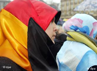 A young Turkish girl wears a headscarf in the colors of the German flag