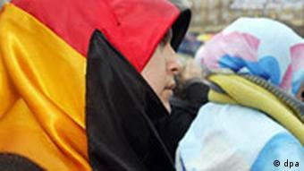 A young woman waring a headscarf in the colors of the German national flag