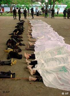 Soldados colombianos observan los cuerpos de rebeldes muertos.