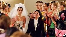 Japanese fashion designer Hanae Mori, center, holds the hand of the bride and acknowledges applause at the end of her Fall/Winter 2004-2005 Haute Couture fashion show in Paris, Wednesday, July 7, 2004. The designer said goodbye to her couture workers as it was her final Paris collection. (AP Photo/Remy de la Mauviniere)
