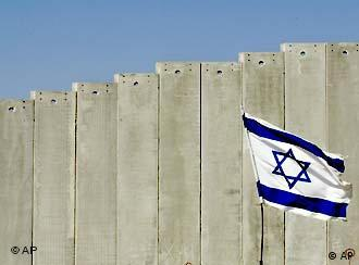 An Israeli flag waves in front of the wall between Israel and the Palestinian territory