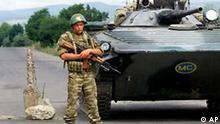 A soldier of Russian peacekeeping forces in South Ossetia stands guard near the Ergneti village on the internal border between Georgia and its breakaway region, Friday, July 9, 2004, with a BMP-1, infantry fighting vehicle in the background. South Ossetia, has run its own affairs - without international recognition - since a 1992 truce ended separatist fighting. Georgian, Russian and South Ossetian forces all conduct peacekeeping operations in the region, which borders the Russian republic of North Ossetia. . (AP Photo/ Shakh Aivazov)