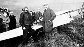 French flyer Louis Bleriot, left, stands in front of his plane after landing near Dover on July 25, 1909