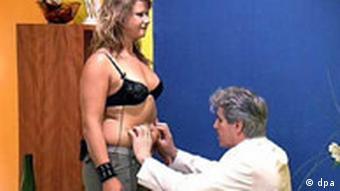 Ein Schönheitschirurg untersucht den Bauch einer Patientin
