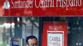 Santander bank sign with man walking in front