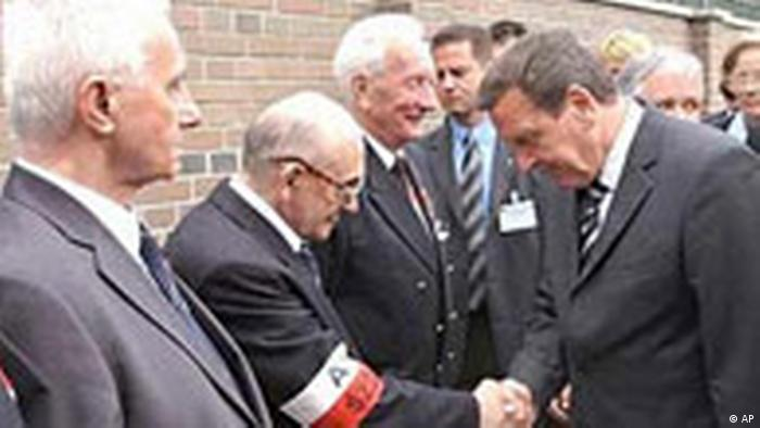 The then German Chancellor Gerhard Schroeder (R), shakes hands with Warsaw Uprising veteran Tadeusz Pospiech at the Warsaw Uprising Museum, 2004