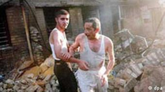 An Iraqi man is helped from rubble outside a church after a car bomb attack in Baghdad