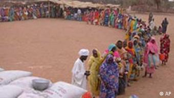 Sudanese displaced woman line up to receive food at Kasab Internally Displaced People's camp near Kutum, Northern Darfur, Sudan in this July 2004 file picture.The European Union has threatened Sudan with imminent U.N. sanctions if it does not end the conflict in its western Darfur region that has killed tens of thousands, but Sudan said the threats would only damage peace efforts.(AP Photo/Marcus Prior/WFP)