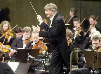 Ein Mann im schwarzen Frack dirigiert ein Philharmonie-Orchester.