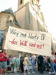 Demonstranten vor der Nikolaikirche halten ein Plakat mit der Aufschrift 'Weg mit Hartz IV - Das Volk sind wir' hoch, Quelle: AP