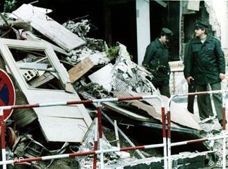 Two West Berlin policemen stand next to a huge pile of rubble outside the Berlin discotheque La Belle