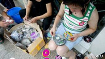 Women sort through copied CDs and DVDs in cardboard boxes in China