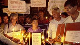 A group of people holding candles and signs against the death penalty