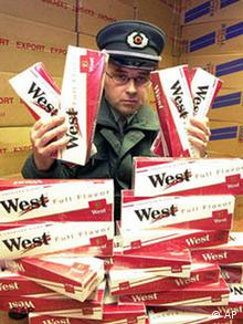 A police officer displays a pile of smuggled cigarette cartons