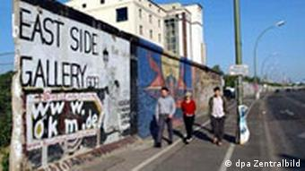 Tourists look through the a segment of the grey Berlin wall that remains from the fall