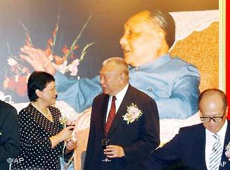 Daughter of late Chinese paramount leader Deng Xiaoping, Deng Nan, left, chats with Hong Kong leader Tung Chee-hwa in front of a portrait of her father during the opening ceremony in Hong Kong, Thursday, Aug. 26, 2004, of an exhibition marking the 100th anniversary of Deng's birth. The exhibit features pictures and personal items of Deng. At right is local tycoon Li Ka-shing. (AP Photo/Anat Givon)