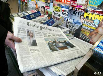 An unidentified person buys a copy of the New York Times at a newsstand Thursday, June 5, 2003 in New York. The New York Times' top two editors resigned Thursday after a tumultuous five weeks that began with the exposure of Jayson Blair's journalistic fraud and grew into a drumbeat of criticism of the management style at one of the world's most distinguished newspapers. (AP Photo/Akira Ono)