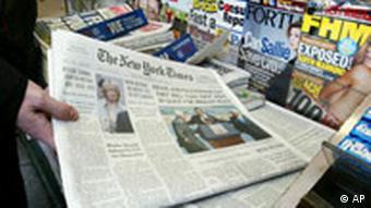 Ein Zeitungsstand, eine Hand greift nach einer Ausgabe der New York Times