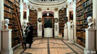 Im berühmten Rokoko-Saal der Herzogin Anna Amalia Bibliothek in Weimar blättert eine Mitarbeiterin der Stiftung Weimarer Klassik und Kunstsammlungen in einem historischen Atlas