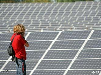 A woman stands in front of rows of solar panels