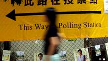 A woman walks past a sign leading to a polling center in the Hong Kong legislative election Sunday, Sept. 12, 2004. Hong Kong people get to directly elect 30 of the territory's 60 lawmakers in the election amid calls for universal suffrage, which Bejing has ruled out at present. (AP Photo/Vincent Yu)