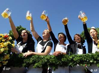 A row of people hold their beers up to the sky at Oktoberfest