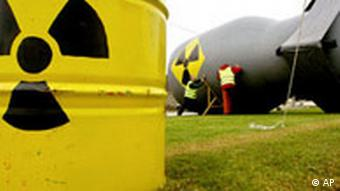 Greenpeace activists adjust a makeshift inflatable giant nuclear bomb as they set up a road checkpoint in Equeurdreville, outside Cherbourg harbour, Normandy, Saturday, Oct. 2, 2004