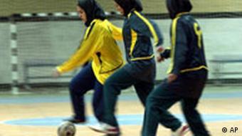 Drei Frauen spielen in einer Sporthalle Fußball
