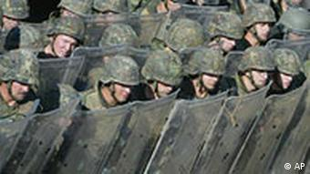Soldiers of Germany's KFOR troops hide behind riot protection shields during an exercise