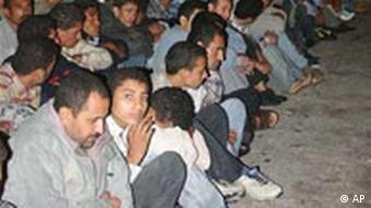 A group of migrants sitting on the ground