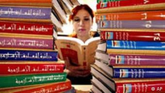 A woman reading between stacks of books.
