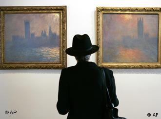 A museum visitor views two paintings in Monet's London Parliament series