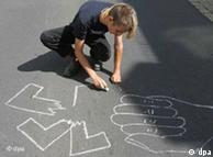 Молодой человек рисует на асфальте разорванную свастику и направленный на нее кулак в знак протеста против демонстрации неонацистов