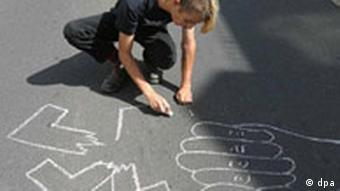 Ein Punk malt ein zerbrochenes Hakenkreuz auf die Straße