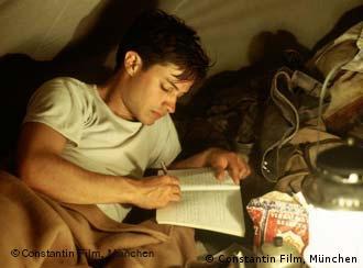 Ein junger Mann liegt in einem Zelt und schreibt in ein Heft