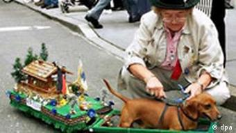 A dachshund with a carriage attached to him that carries a German alpine cottage