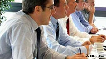 Men in ties and shirt-sleeves attend a training course