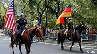 Police officers on horseback carrying a German flag and an American flag