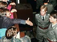 Alemães orientais estendem a mão a guardas de fronteira no Checkpoint Charlie