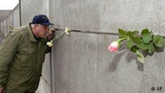 A man peering through a gap between two concrete plates as he looks through the former Berlin Wall