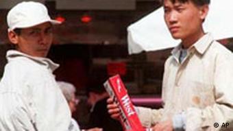 Junge Vietnamesen in Berlin bieten eine Stange geschmuggelter Zigaretten der Marke West an (AP Photo / Jockel Finck)