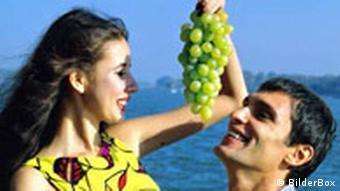 Flirten Junge Frau verführt Ihren Freund mit Weintrauben