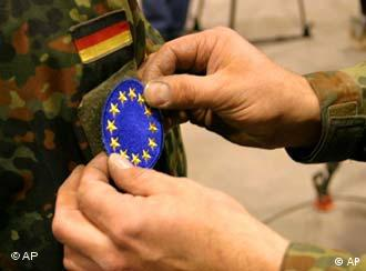 A German Army officer, member of peacekeeping forces in Bosnia, places a new EUFOR signet on the uniform sleeve of a fellow soldier at the German military base