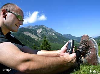 A man in the Alps looking at a handheld GPS receiver