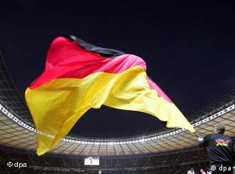 A German flag being unfurled in a soccer stadium