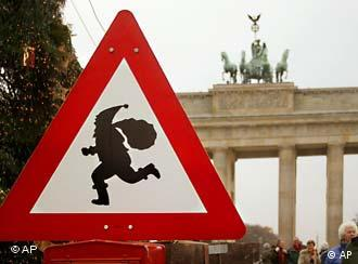 A street sign with an image of Santa Claus, in front of Berlin's Brandenburg Gate