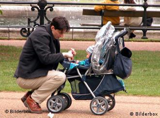 Ein Vater mit einem Kinderwagen im Park